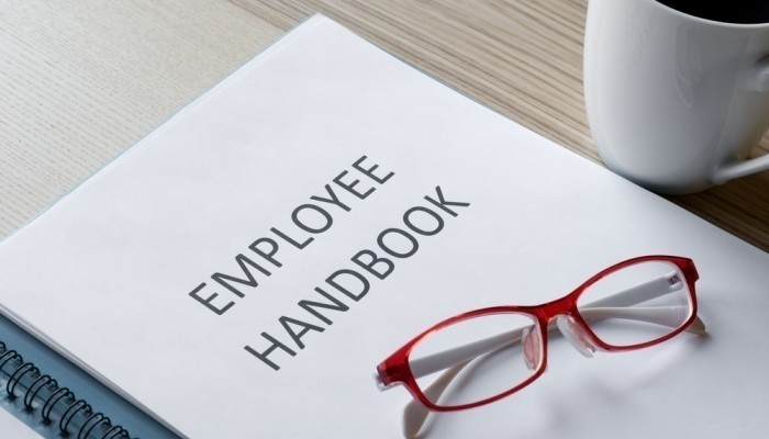 Employee handbook with reading glasses
