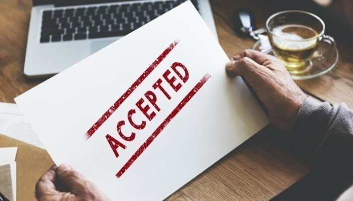 Close-up of a man holding a sheet of paper that has the word 'accepted' written on it