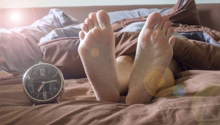 feet and clock on bed