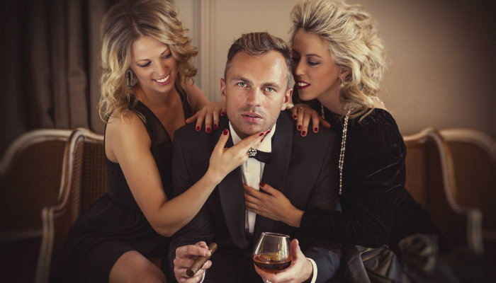 Man being adored by two glamorous women