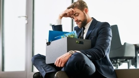 fired  sad man sitting down with box