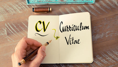 Hand writing CV in notebook