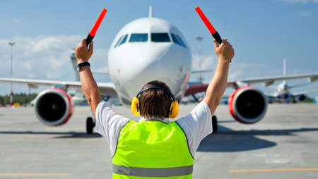 Ground crew employee signalling commercial aircraft into position at airport
