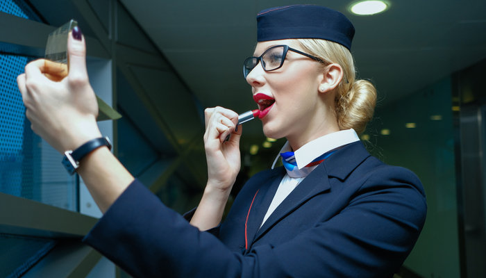 Young female flight attendant applying red lipstick with pocket mirror