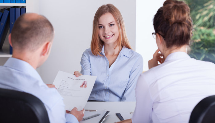 Young woman giving her CV to potential employers at a job interview