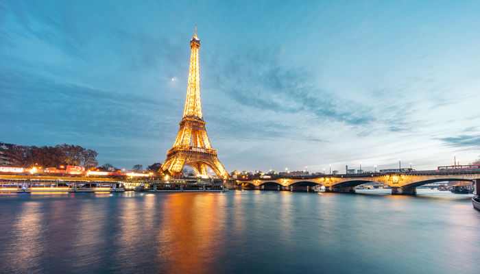 The Eiffel Tower in Paris illuminated at night from view across the Seine