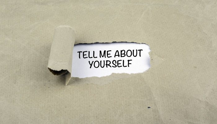 Ripped paper reveals the sentence 'tell me about yourself' on old paper