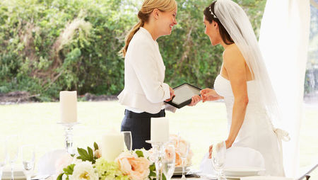 Wedding planner discussing plans with bride on wedding day