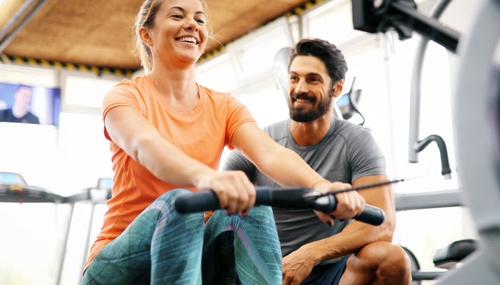 Male personal trainer working with female client in gym