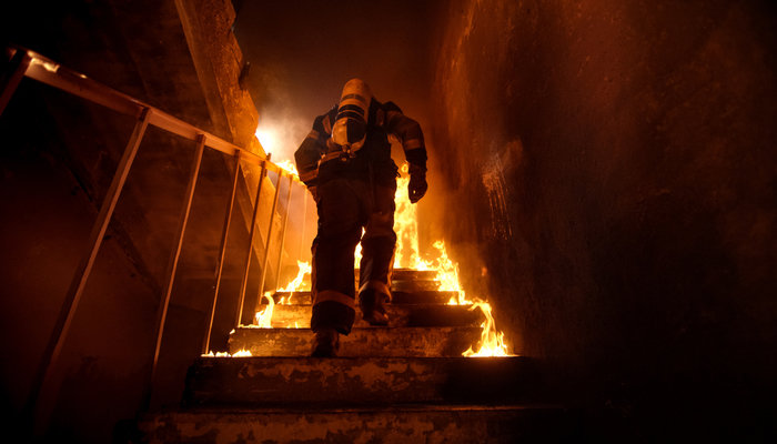 Firefighter climbing stairs in burning building