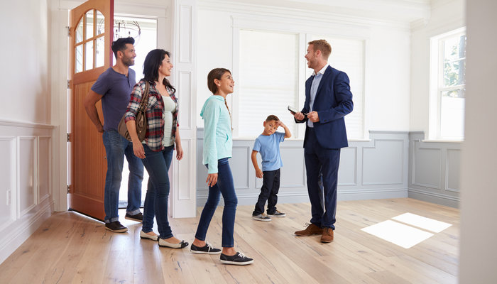 Male real estate agent showing a house to a young family