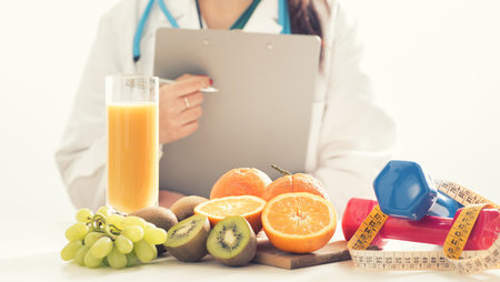 Female dietitian holding a clipboard with fruit and dumbbells placed on a desk