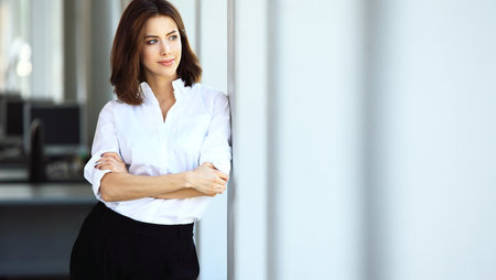 Confident business woman looking out of office window