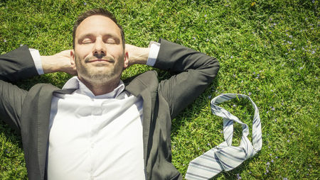 Smiling businessman lying on grass