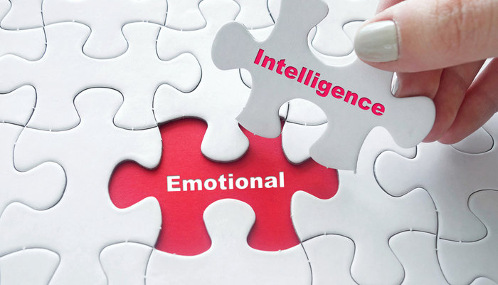 Close-up of a woman's hand placing the final piece of a puzzle that says 'emotional intelligence'