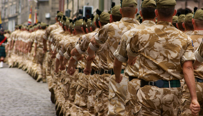 British Army soldiers wearing desert camouflage marching in a public street