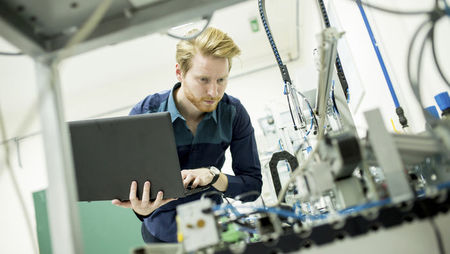 A young male engineering checking machinery and typing on a laptop