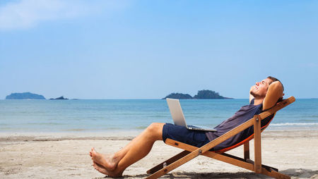 A young man relaxing in a deck chair on the beach with a laptop