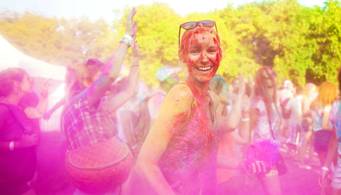 A smiling young woman celebrating the Holi Festival