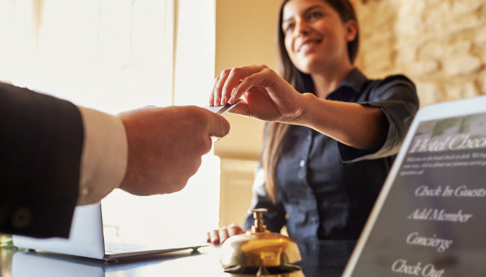 A female receptionist giving a male guest his keycard