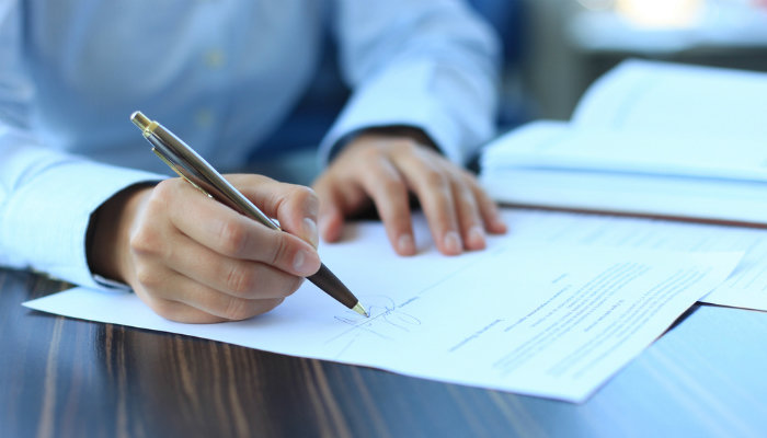 A close-up of a businessman signing a contract
