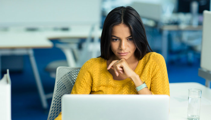 A young woman wearing a yellow sweater working on a laptop